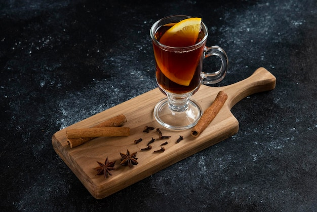Een glazen kopje thee en met kaneelstokjes en steranijs.