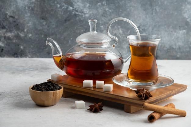 Een glazen kopje thee met suiker en steranijs.