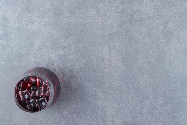 Een glazen kopje vers granaatappelsap met ijsblokjes. hoge kwaliteit foto