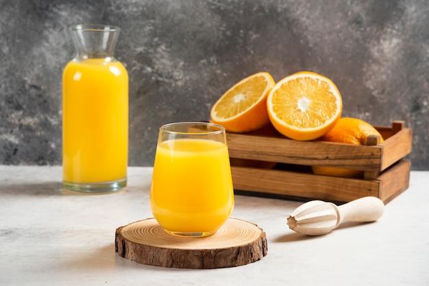 Een glazen kopje vers sinaasappelsap op een houten bord.