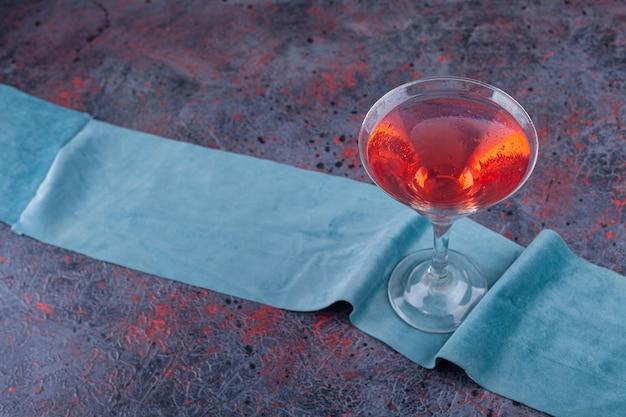 Een glazen kopje vruchtensap op een tafelkleed.