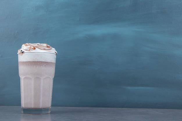 Een glazen kopje zoete milkshake met slagroom. hoge kwaliteit foto
