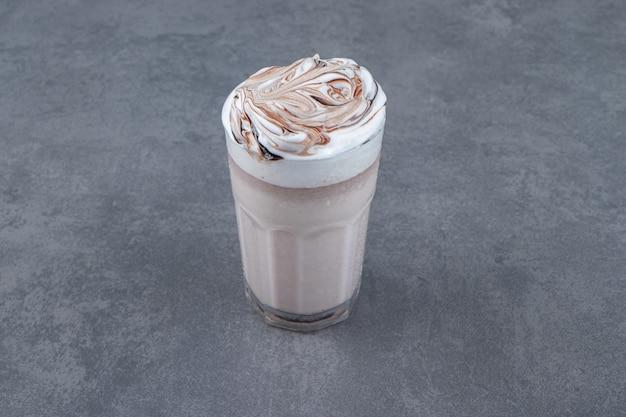 Een glazen kopje zoete milkshake met slagroom.