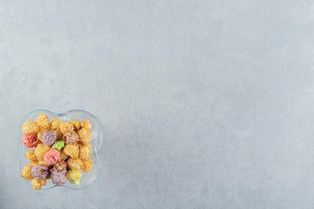 Een glazen kopje zoete veelkleurige popcorn.