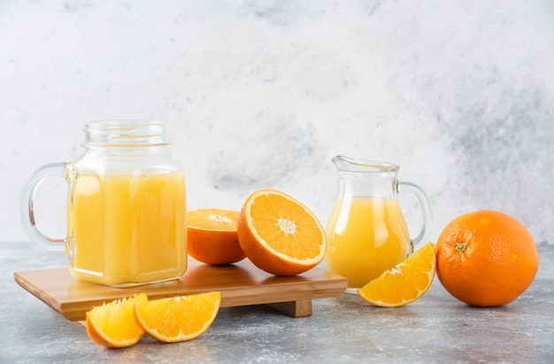 Een glazen kruik sap met vers oranje fruit op stenen tafel.