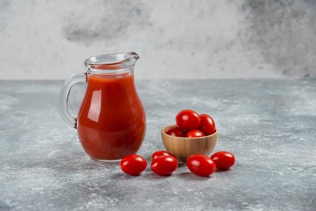 Een glazen kruik vol tomatensap met een houten kom met cherrytomaatjes.