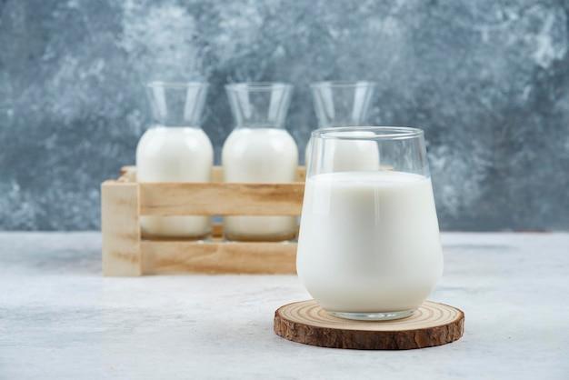 Een glazen melk op een grijze tafel.