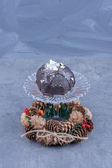Een glazen plaat met een chocoladetaart en dennenappels