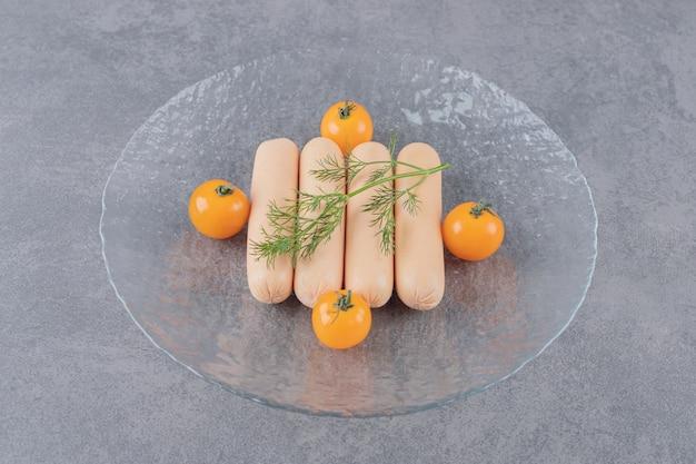 Een glazen plaat van gekookte worst met gele kersentomaten
