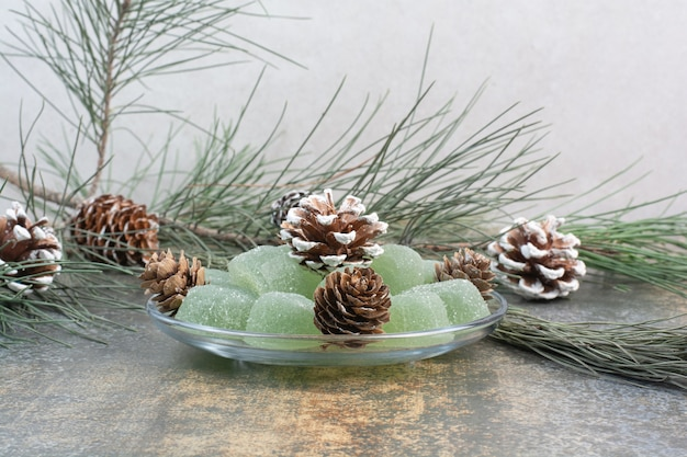 Een glazen plaat van groene marmelade en dennenappels. hoge kwaliteit foto