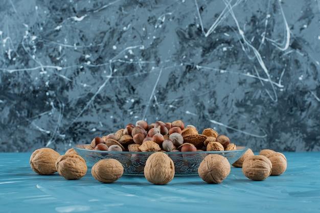 Een glazen plaat vol met verschillende soorten gezonde verse noten op een blauwe achtergrond.