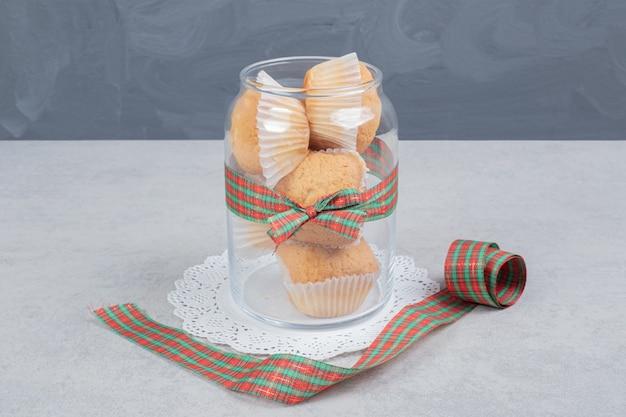 Een glazen pot cupcakes op wit oppervlak.