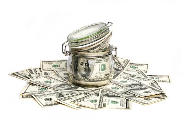 Een glazen pot gevuld met dollars onder honderd-dollarbiljetten op een witte achtergrond.