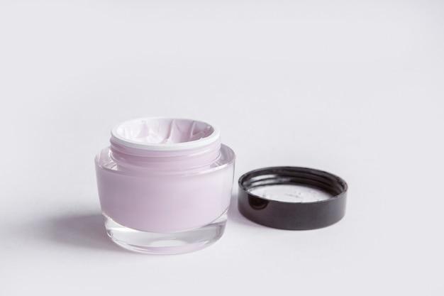 Een glazen pot huidcrème op een witte achtergrond.