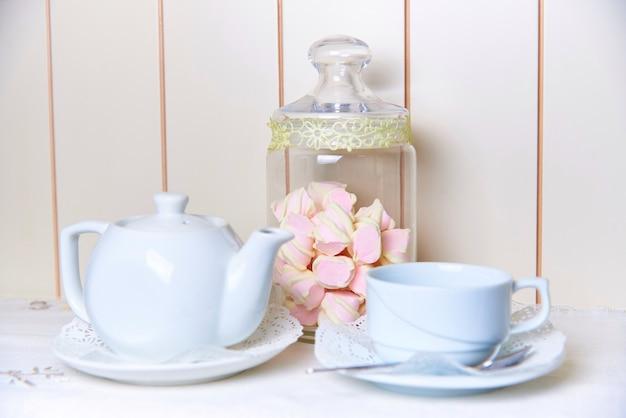 Een glazen pot marshmallow staat achter een ketel en een kop op een schotel met kant.