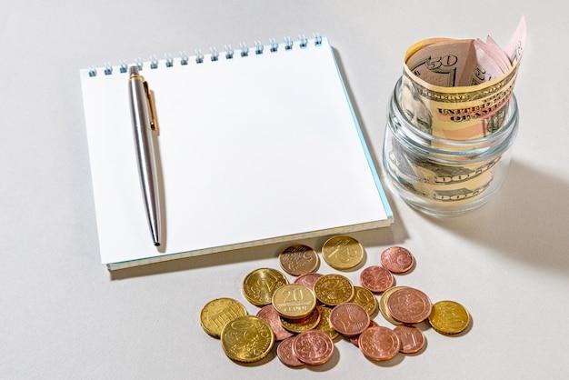 Een glazen pot met amerikaanse dollars, verspreide munten en een notitieboekje om mee te schrijven. financiën concept