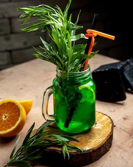 Een glazen pot met dragon drankje gegarneerd met dragon en schijfje citroen