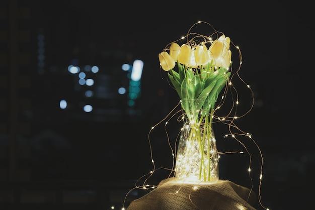 Een glazen pot met een bos tulpen omringd met een reeks lichten met gouden warme lichten gloeien