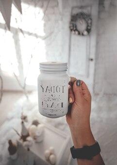 Een glazen pot met een drankje in de handen van een vrouw. de levensstijl, de sfeer van kerstmis kopieer ruimte voor uw tekst.