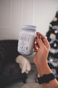 Een glazen pot met een drankje in de handen van een vrouw de levensstijl de sfeer van kerstmis