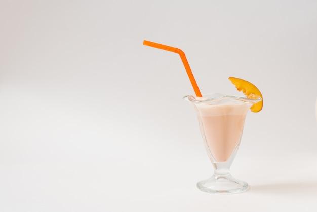 Een glazen pot met een oranje plastic buis en een mooie lichtoranje milkshake erin. een glas met een stuk nectarine op een witte achtergrond.