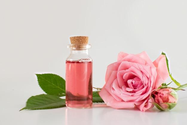 Een glazen pot met een roze roos