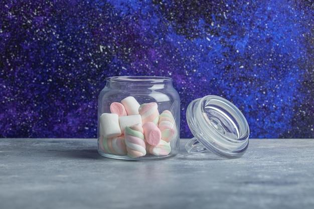 Een glazen pot met heerlijke marshmallows op een grijze achtergrond.