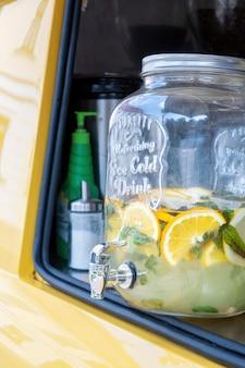 Een glazen pot met kraan vol limonade met citroen en munt in gele foodtruck, close-up. zomerdrankje met ijs in mobiele retro coffeeshop.