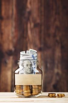 Een glazen pot met munten en een honderd dollar biljet, een sticker met vrije ruimte voor tekst, op een houten tafel.