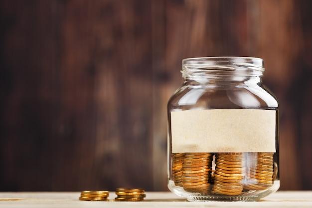 Een glazen pot met munten en een sticker met vrije ruimte voor tekst op houten tafel.