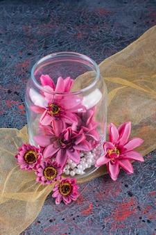 Een glazen pot met paarse bloemen met parels op geel tafelkleed.