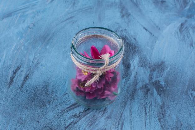 Een glazen pot met paarse kunstmatige bloemen op blauw.