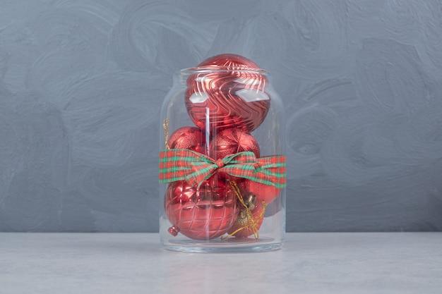 Een glazen pot met rode kerstballen op donkere achtergrond.