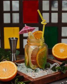 Een glazen pot met sinaasappel-, citroen- en grapefruitscocktail met plakjes fruit.