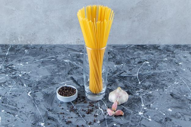 Een glazen pot rauwe droge spaghetti met knoflook en peperkorrels.