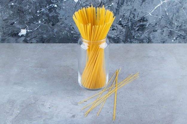 Een glazen pot rauwe droge spaghetti op een stenen achtergrond.