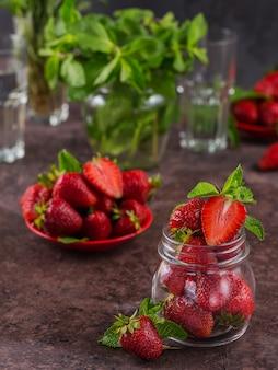 Een glazen pot rode sappige aardbeien op donkerbruine tafel