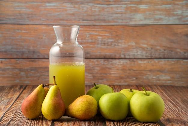 Een glazen pot sap met groene appels en peren eromheen