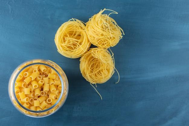 Een glazen pot vol ditali rigati en schelpvormige pasta met rauwe nestnoedels.