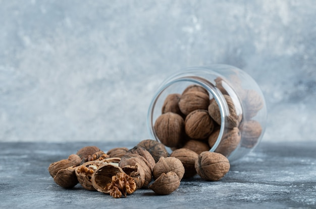 Een glazen pot vol gezonde walnoten op een grijze achtergrond.