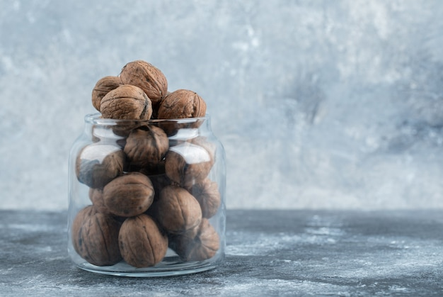 Een glazen pot vol gezonde walnoten op een marmeren achtergrond.