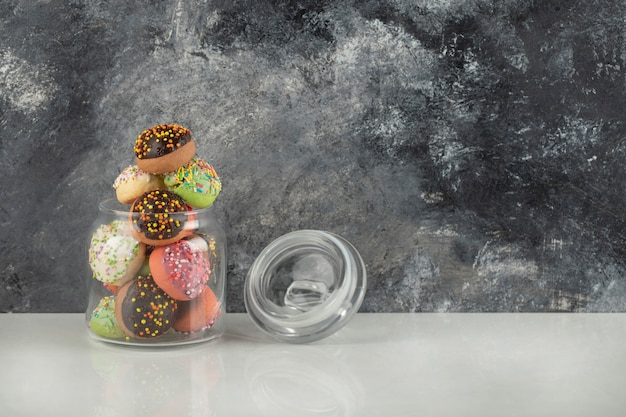 Een glazen pot vol kleine kleurrijke donuts.