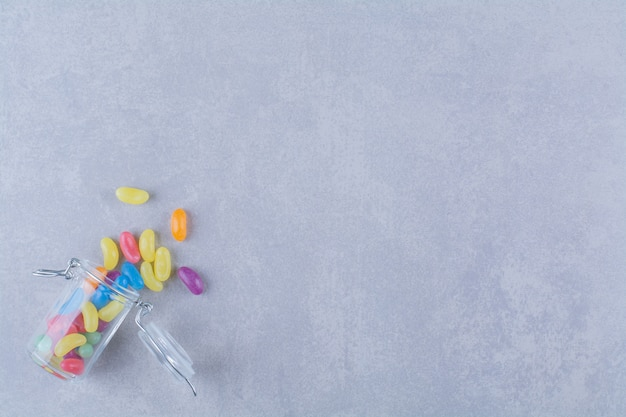 Een glazen pot vol kleurrijke bonensnoepjes