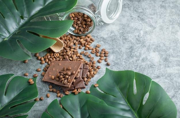 Een glazen pot vol koffiebonen met chocoladerepen op een grijze achtergrond.