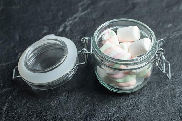 Een glazen pot vol marshmallows op een donkere ondergrond.