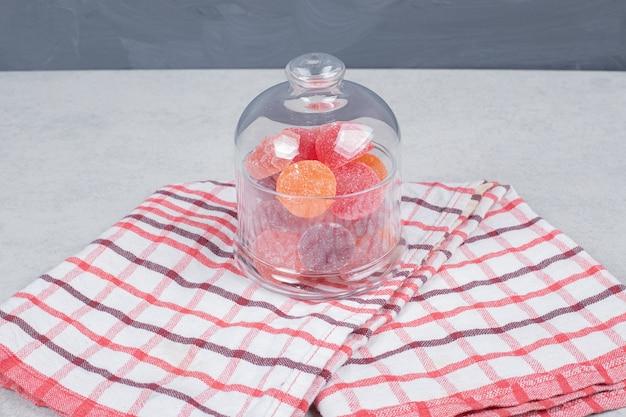 Een glazen pot zoet snoep op rood tafellaken. hoge kwaliteit foto