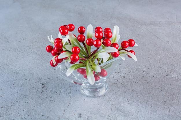 Een glazen schaal vol rode rozenbottels op grijs