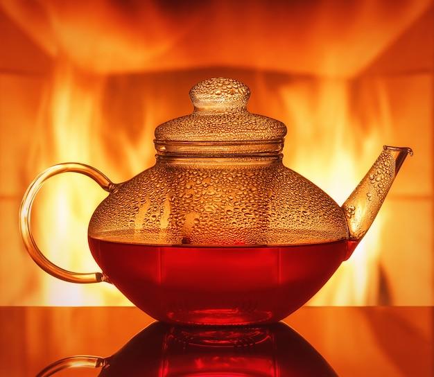 Een glazen theepot aan de tafel voor een open haard