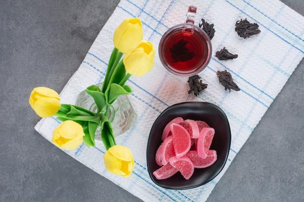 Een glazen vaas met bloemen met kopje thee en marmelade.