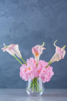 Een glazen vaas met boeket roze mooie verse bloemen.